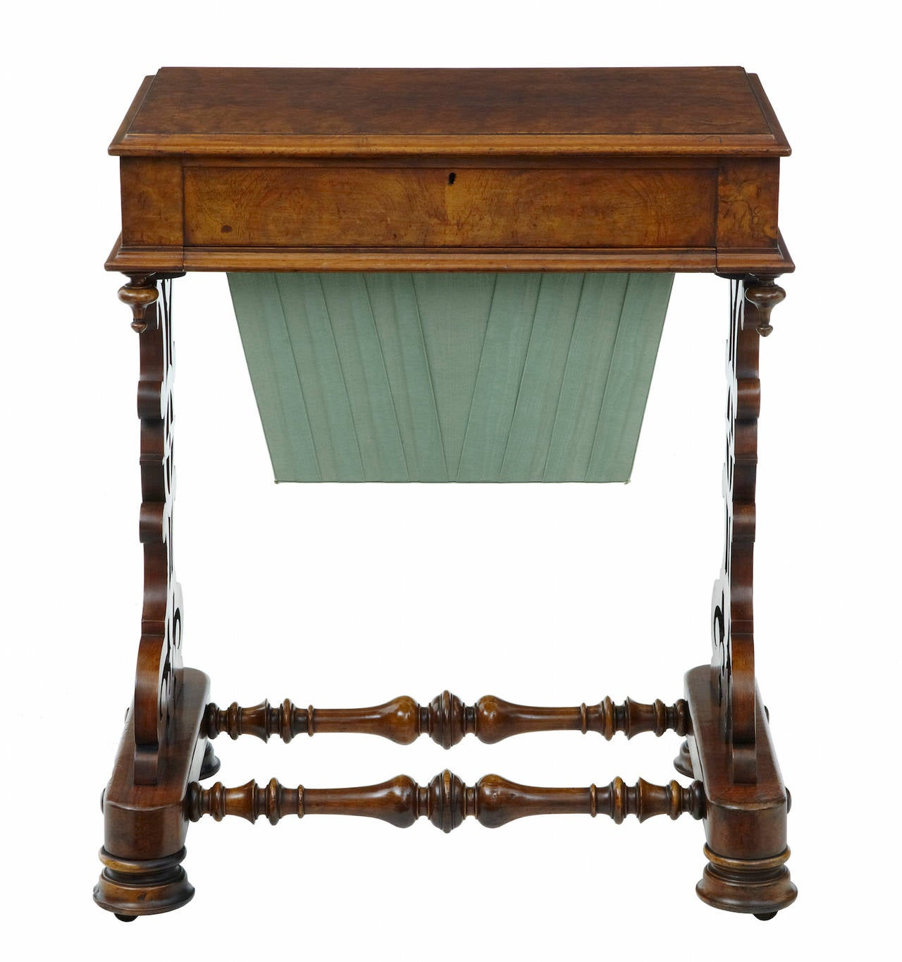 High Victorian ladies work table, circa 1870. Beautiful walnut work table of good color and patina. Satinwood interior with fretwork covered compartments. The interior is echoed by the fretwork legs, united by turned stretchers. Standing on