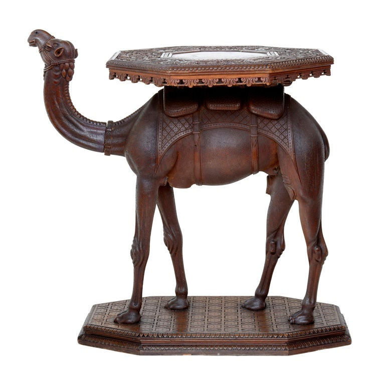 Antique carved octagonal low table resting on a camel at