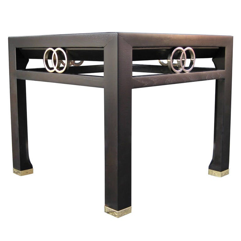 Pair of stunning side / end tables with ebonized finish and brass sabots by Michael Taylor for Baker Furniture. Unusual styling with channeled detailing around the perimeter of the top and tapered legs that widen at the brass capped foot. The