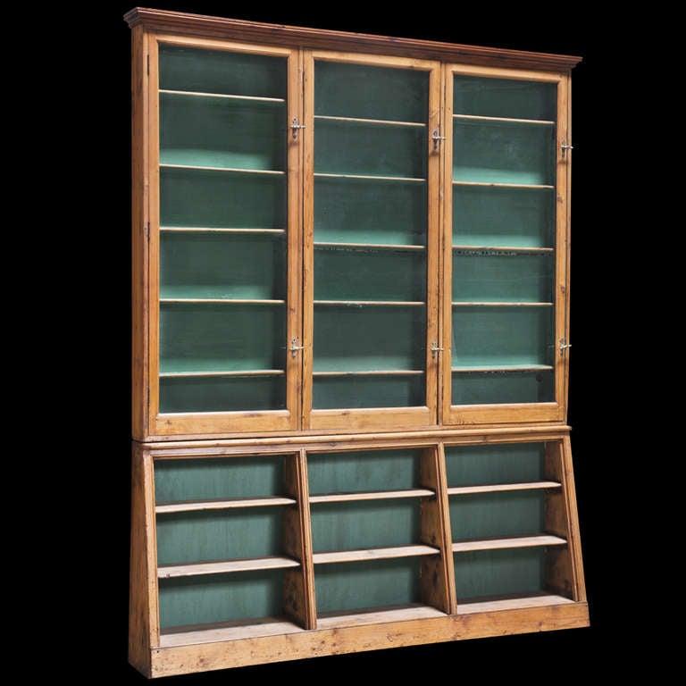 Unusually narrow cabinet with original green painted back drop behind shelves, original glass doors