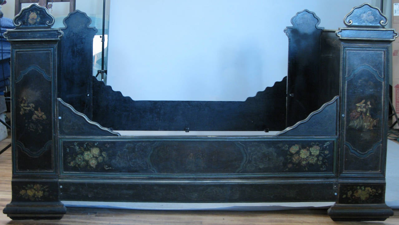 a romantic and bold antique Victorian cast iron bed with tall head and foot, and entirely hand painted with floral and figural motifs.