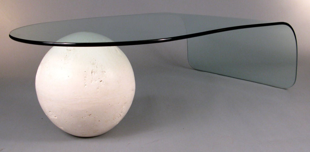 a unique cocktail table designed with a surface of curved glass, supported on one end by a white plaster sphere. very well made and in excellent condition.