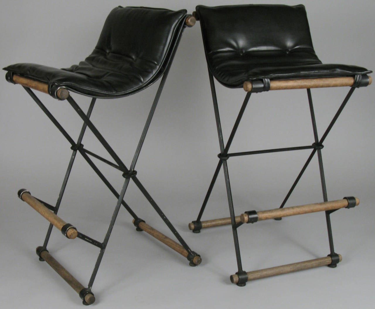 A pair of Classic 1970s iron X-frame Campaign barstools by California designer Cleo Baldon, with oak stretchers and button tufted upholstered seat cushions.