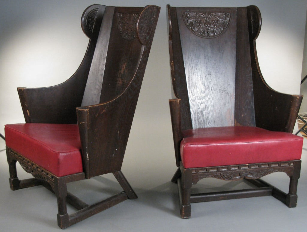 a wonderful pair of antique 1930's carved and panelled wood wing chairs by Jamestown Lounge Company, with angeled legs and base with tall back with curved sides and scrolled arms. detailed carved panels around the top