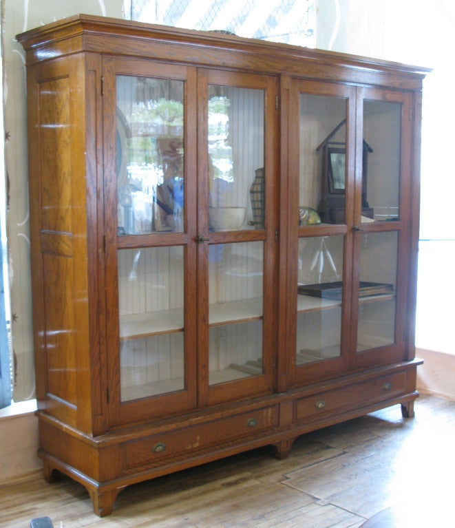 a beautiful antique 1920's oak display storage case with 2 pairs of hinged glass doors, and 3 adjustable interior shelves, as well as 2 long drawers below. beautifully grained oak and very handsome proportions. perfect for a wide variety of home or