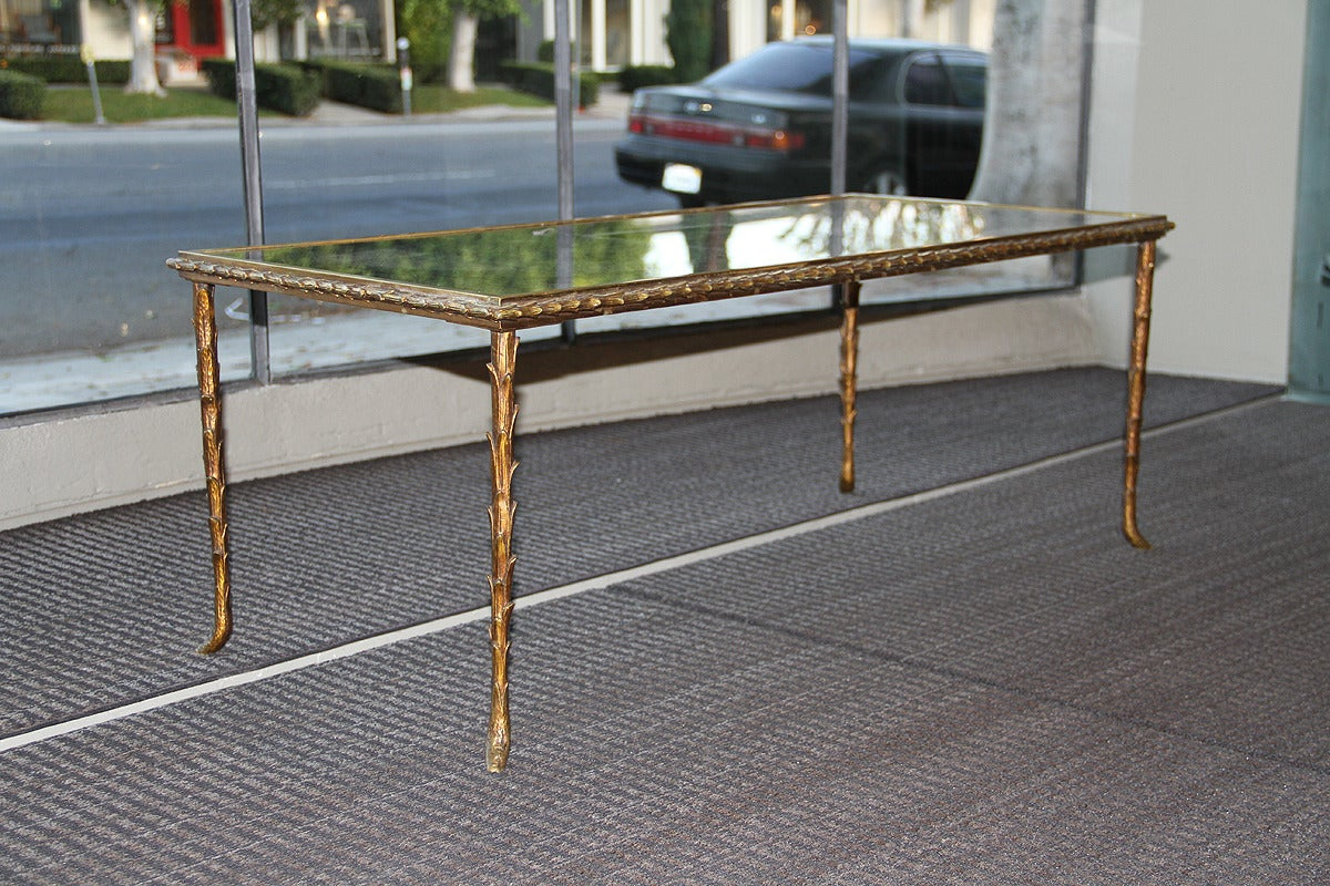 Maison Baguès.  This very elegant Baguès coffee table is in its original condition, it has a gilt bronze, palm trunk motif frame and an églomisé mirrored top. The feet on each leg and the edge have a ram horn shape. The bronze has a beautiful