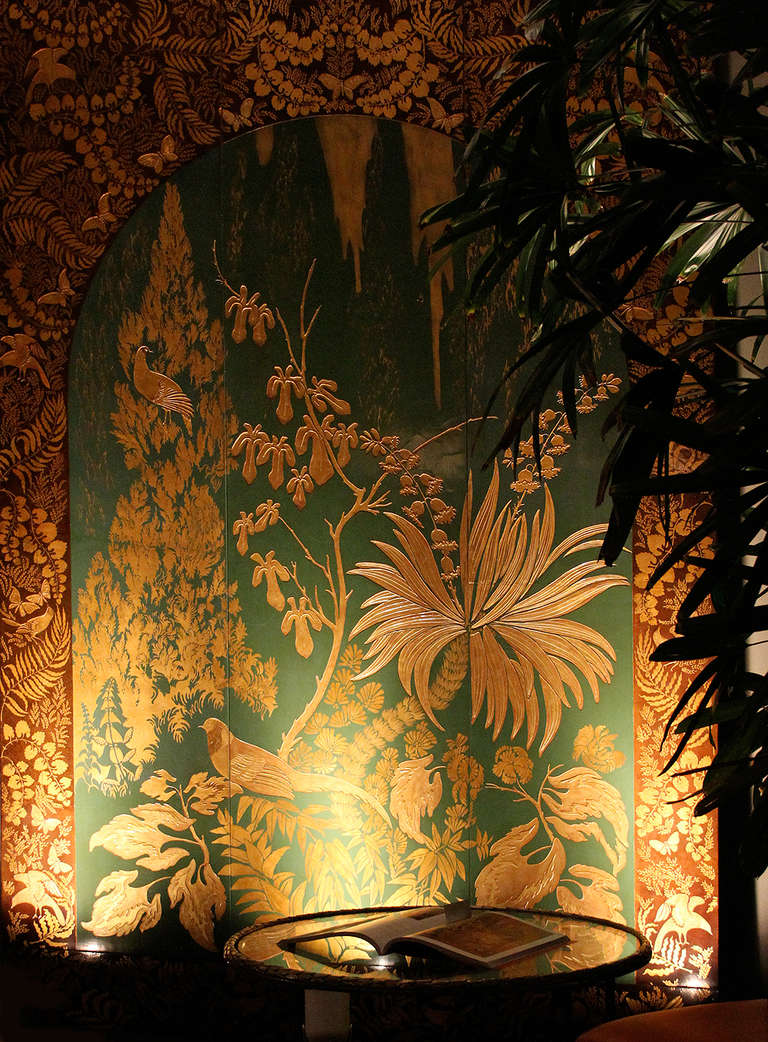ARMAND-ALBERT RATEAU (1882-1938): Lacquered Panel - Museum Quality - One-of-a-kind  Exceptional panel depicting a luxuriant forest with birds of paradise and flights of butterflies incised and lacquered in matte and glossy gold on a jade green and