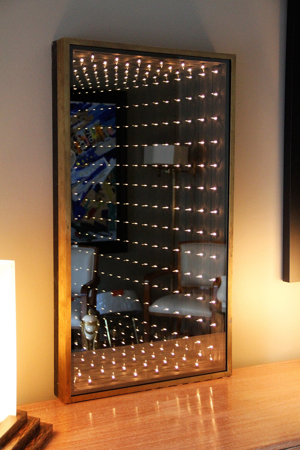 Original and authentic 1970s Infinity mirror, black painted wood structure, brass framed. When the mirror is illuminated, it creates the illusion of infinity depth.  H.36