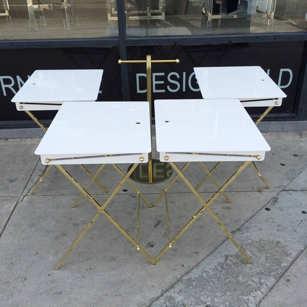 Beautiful set of four serving trays and stand designed by Charles Hollis Jones. The trays are executed in white Acrylic and solid brass, these trays are one of the 20 pieces specifically designed for Lucille Ball and that became the