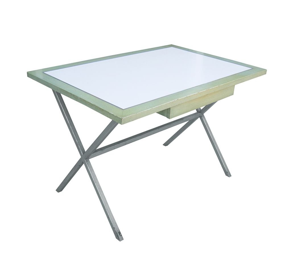 Vintage 1960s Spencer and Company Hollywood Regency desk mounted on a metal base with a silver leaf finish. The top is finished in a combination of green and white colors with a silver trim. The desk has one drawer to store pencils and other