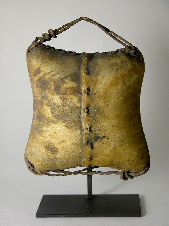 A pouch of sewn rawhide with its volume pillowed and petrified containing   the unopened contents of what was once to cure into cheese.