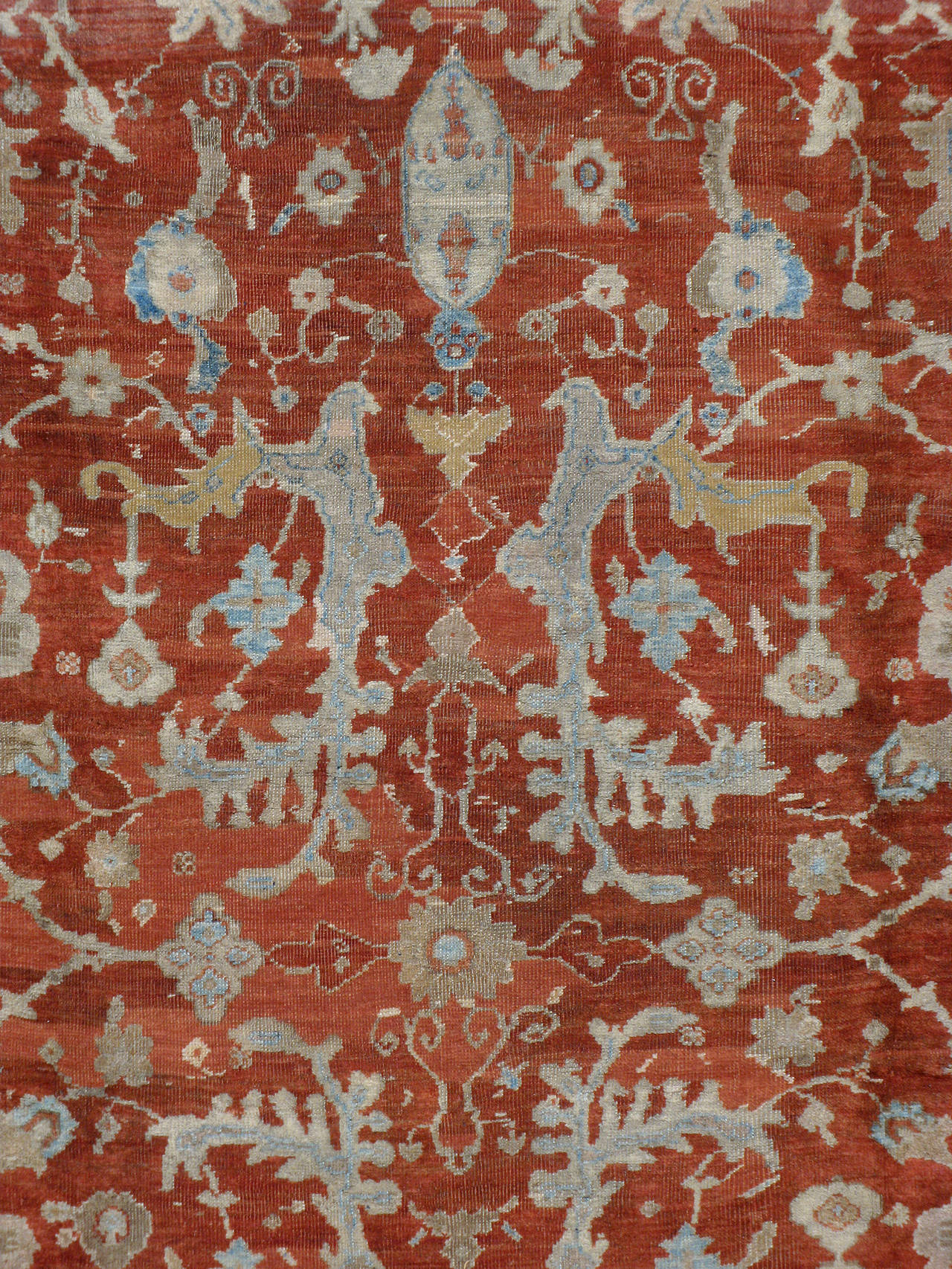 An antique Persian Sultanabad carpet from the turn of the 20th century. A subdued ivory border and designs in soft-pastel hues contrast against the bold crimson red field.