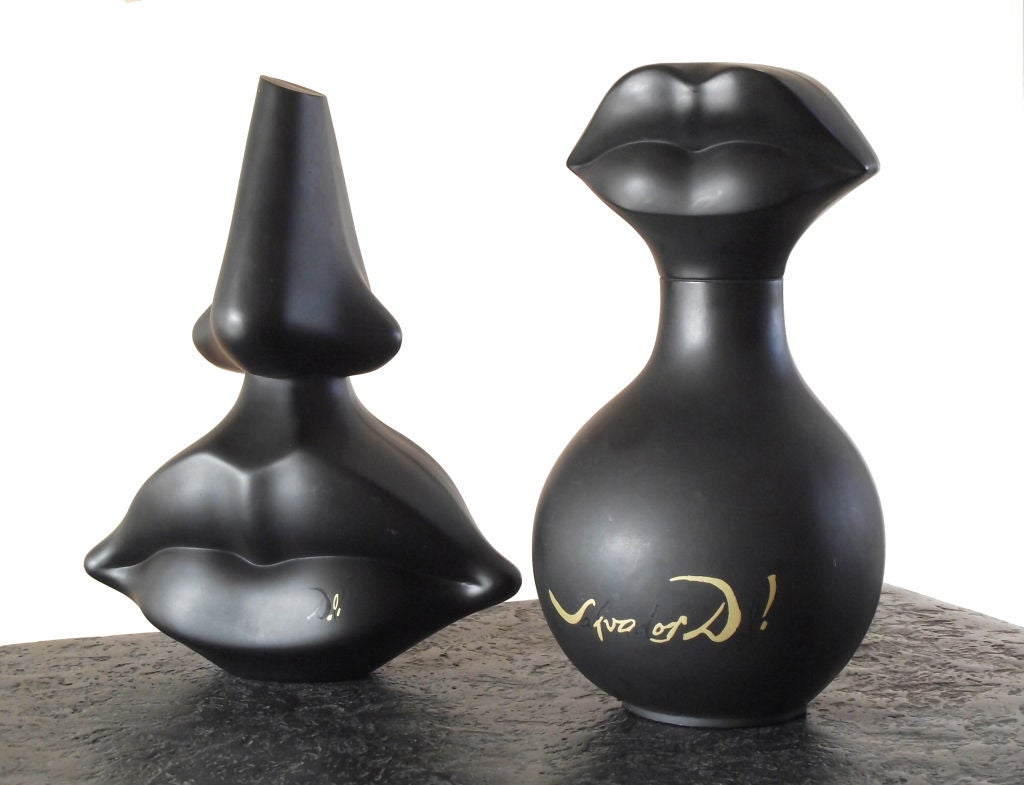 """A pair of Surrealist tabletop sculptures that were created solely for use as promotional store displays for the release of Salvador Dali's """"Salvador Dali"""" perfume. The now-iconic perfume bottle forms were modeled after the nose and lips of"""
