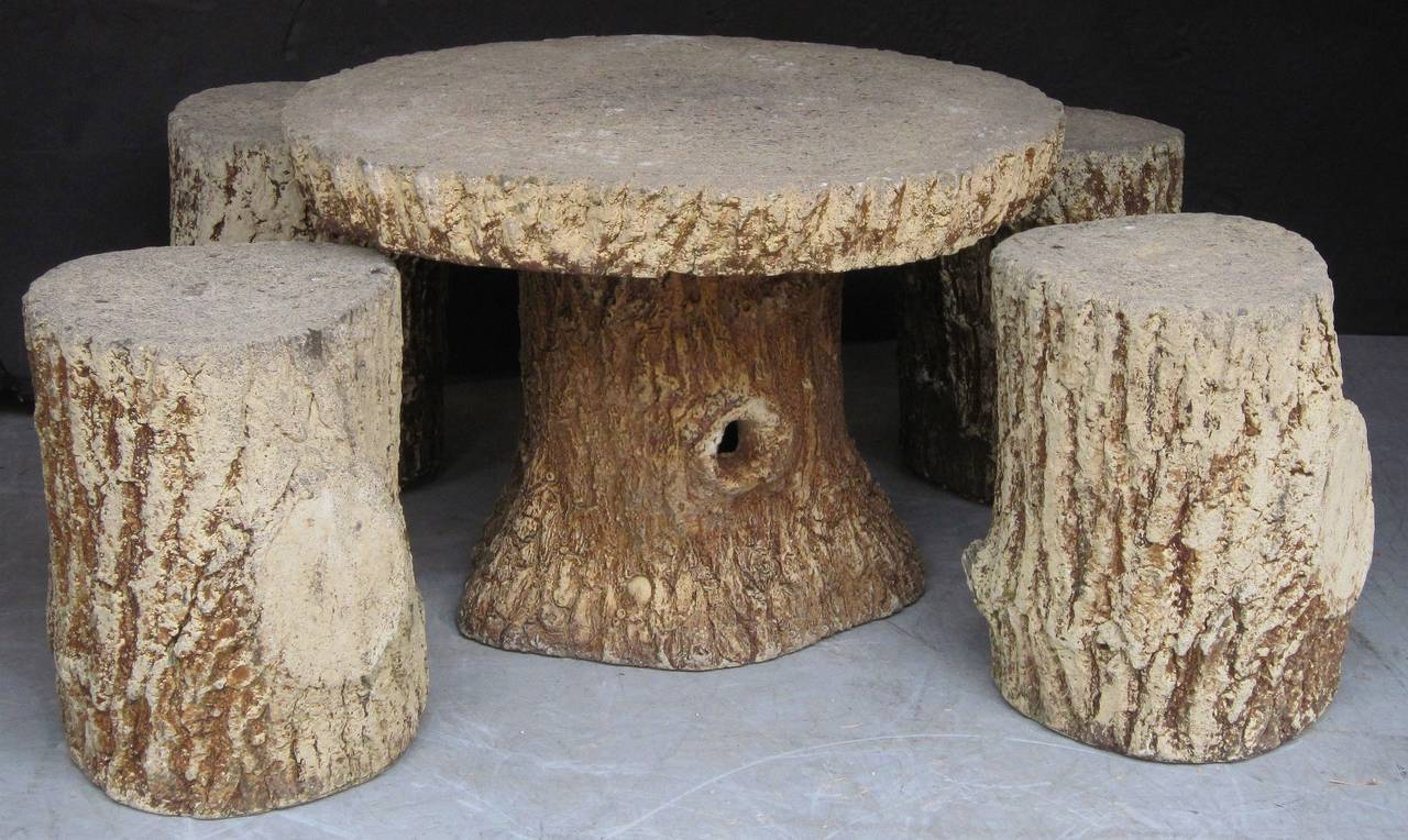 A lovely French faux bois garden stone set (includes table and four stools) - each piece featuring a naturalistic relief design of a tree trunk. Of composition stone.  Table dimensions: approximately height 21 inches x diameter 30 inches Each
