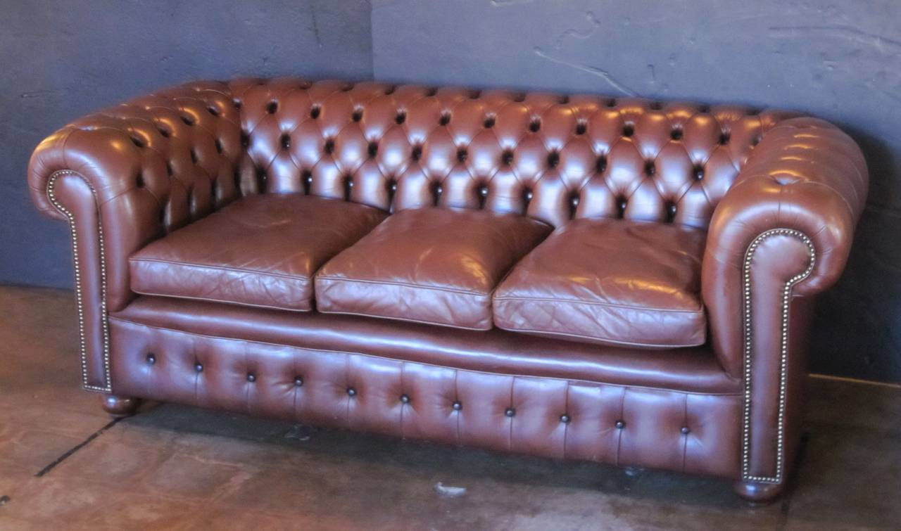 A fine English Chesterfield sofa in vintage brown leather featuring button-tufted back and arms, three soft leather fitted seat cushions, and beaded-nail trim design, resting on turned feet.  The Chesterfield sofa is a classic, synonymous with