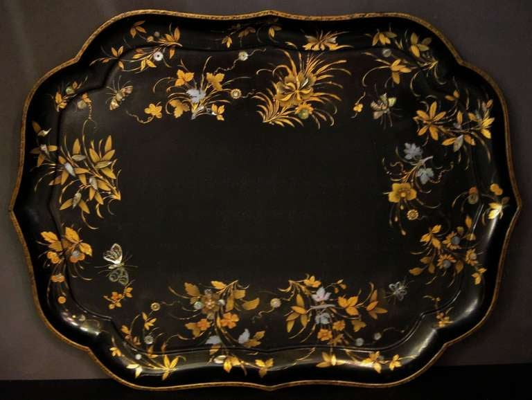 A large English moulded tray of lacquered (japanned-black) papier mâché featuring an Aesthetic Movement design of gilt and mother-of-pearl flowers, grasses and butterflies around the circumference.