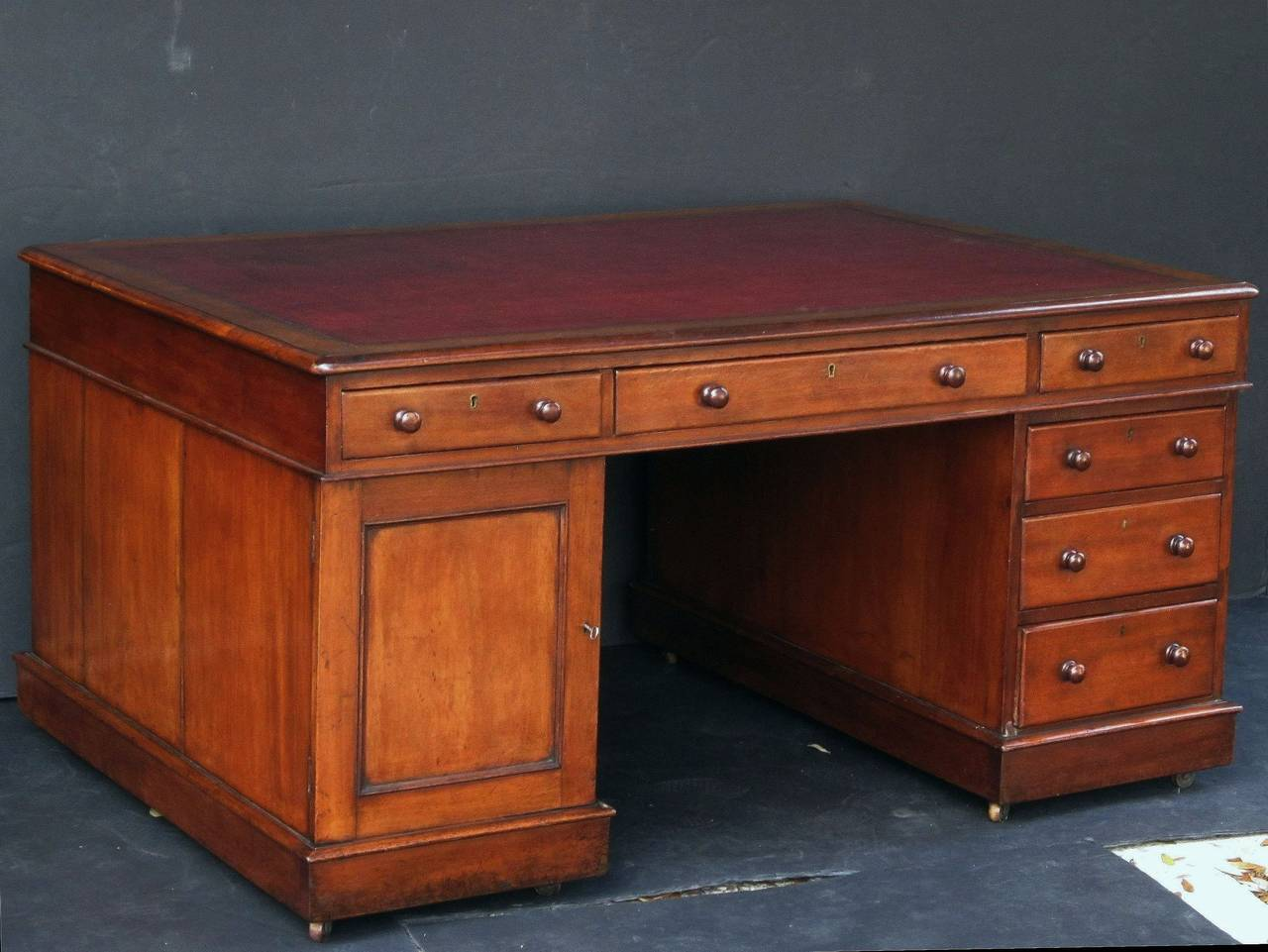 A handsome large English partner's desk of mahogany, featuring a moulded top inset with an embossed red leather, over a long drawer flanked by two short drawers on opposing sides. 