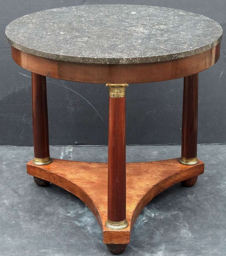 "A handsome French round table or guéridon (30 1/2"" diameter), in the Empire style featuring a circular top of figured black marble set upon a tripod column support of mahogany with brass ormolu fittings, resting on ball feet."