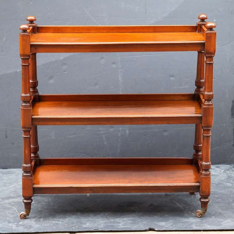 A trolley server (or dumb waiter) of mahogany featuring three tiers with edge-moulded tops, each with back gallery frieze, each tier adjoined to four turned column supports topped with finials, set upon rolling brass casters.