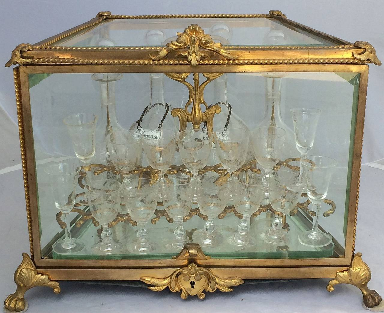 A handsome French Tantalus drinks set or Cave à Liqueur featuring a cabinet of gilt bronze and beveled glass with a mirrored glass base, housing a removable bronze doré stand, holding sixteen etched cordial or liqueur glasses and four etched