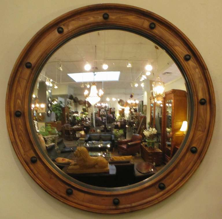 A large English convex mirror (58 3/4 inches diameter) featuring a toned, moulded wood frame with black accents.