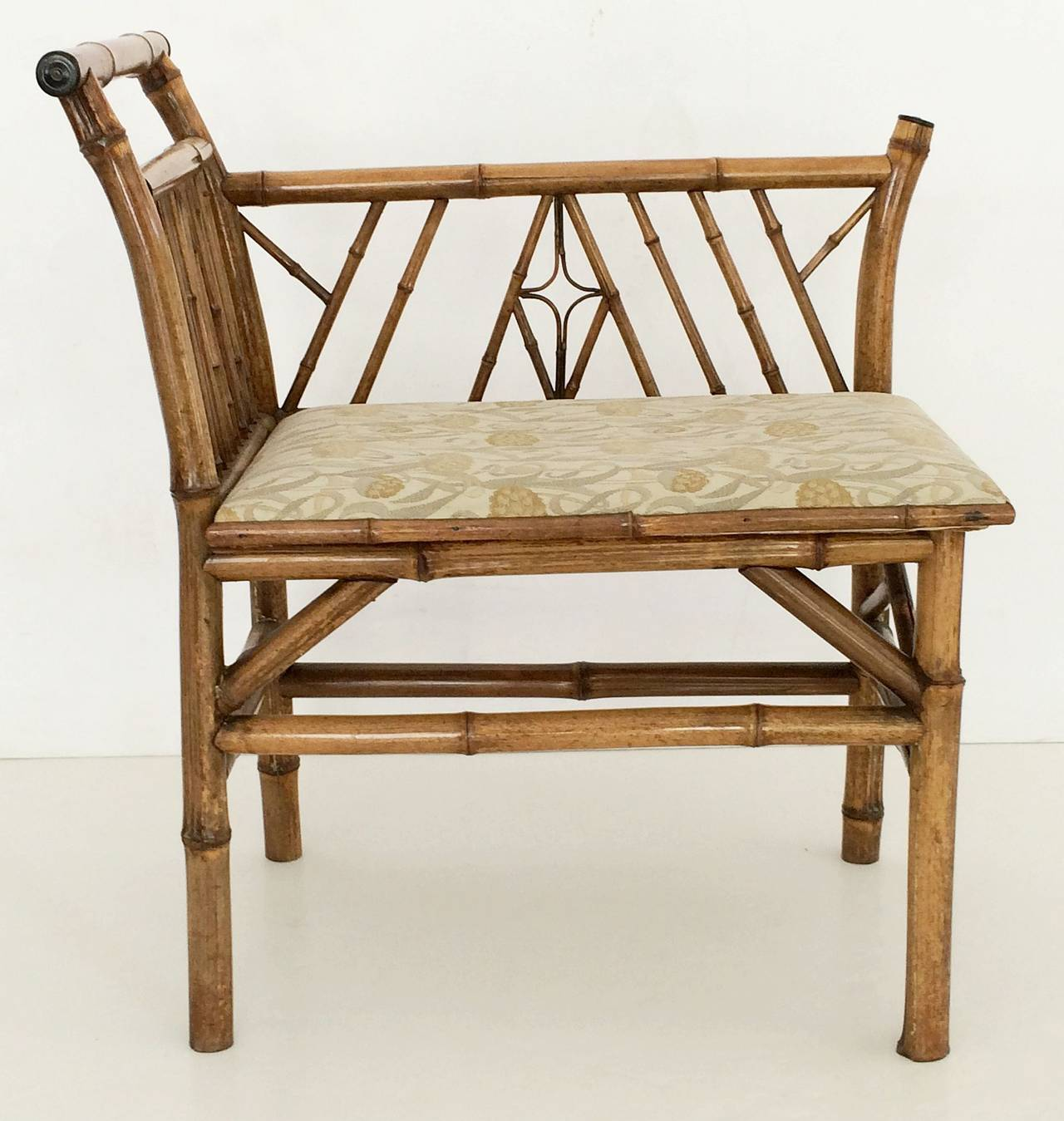A handsome English bamboo bench seat from the Aesthetic Movement period, featuring a slatted back and side of bamboo with an upholstered seat, on sturdy bamboo stretcher.