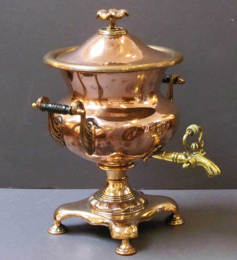 A large French samovar (or tea urn) of copper and brass, featuring a removable domed top with finial, a lovely copper and brass body with ebonized wood handles, a large brass spigot with bone tap, mounted to a footed base.