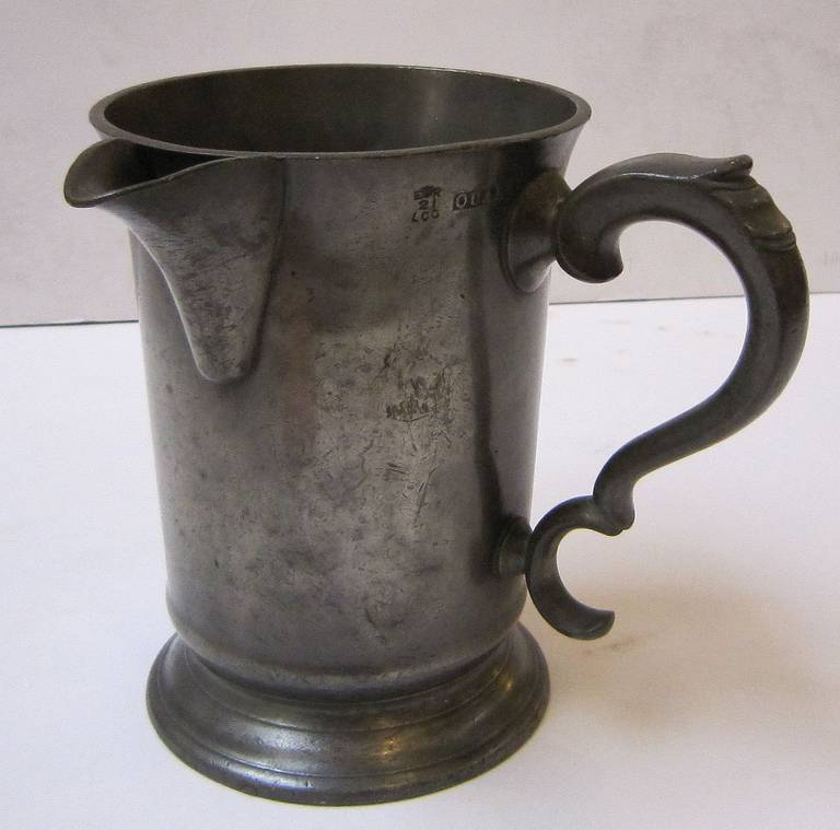 A handsome English pewter tankard or flagon quart ale measure featuring a pour spout and stylish handle, with customs and excise- crown markings.