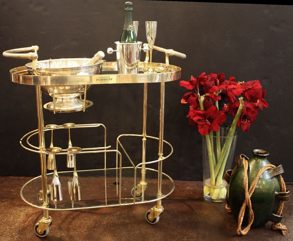 An Art Deco champagne trolley or rolling bar cart featuring a two-tiered curved frame of chromed brass and glass, the top tier with fitted silver bowl or wine cooler for ice, the second tier with six champagne flutes of silver and brass and Art Deco