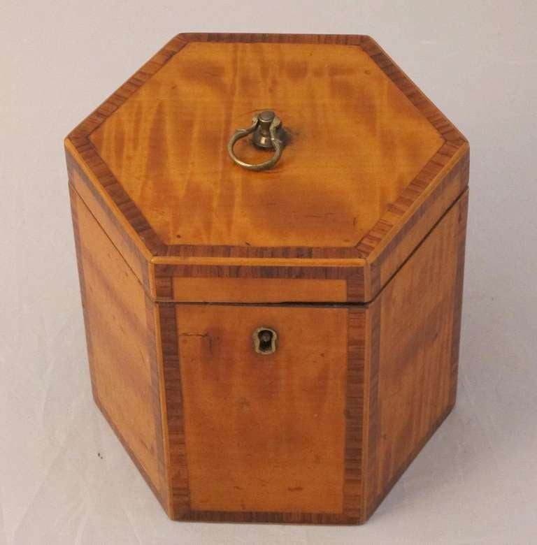 A handsome hexagonal English tea caddy of inlaid satinwood from the Georgian-era featuring a top with perimeter inlay surrounding a metal pull ring, the front with a similar inlay surrounding a brass keyhole escutcheon. Interior with zinc lining.