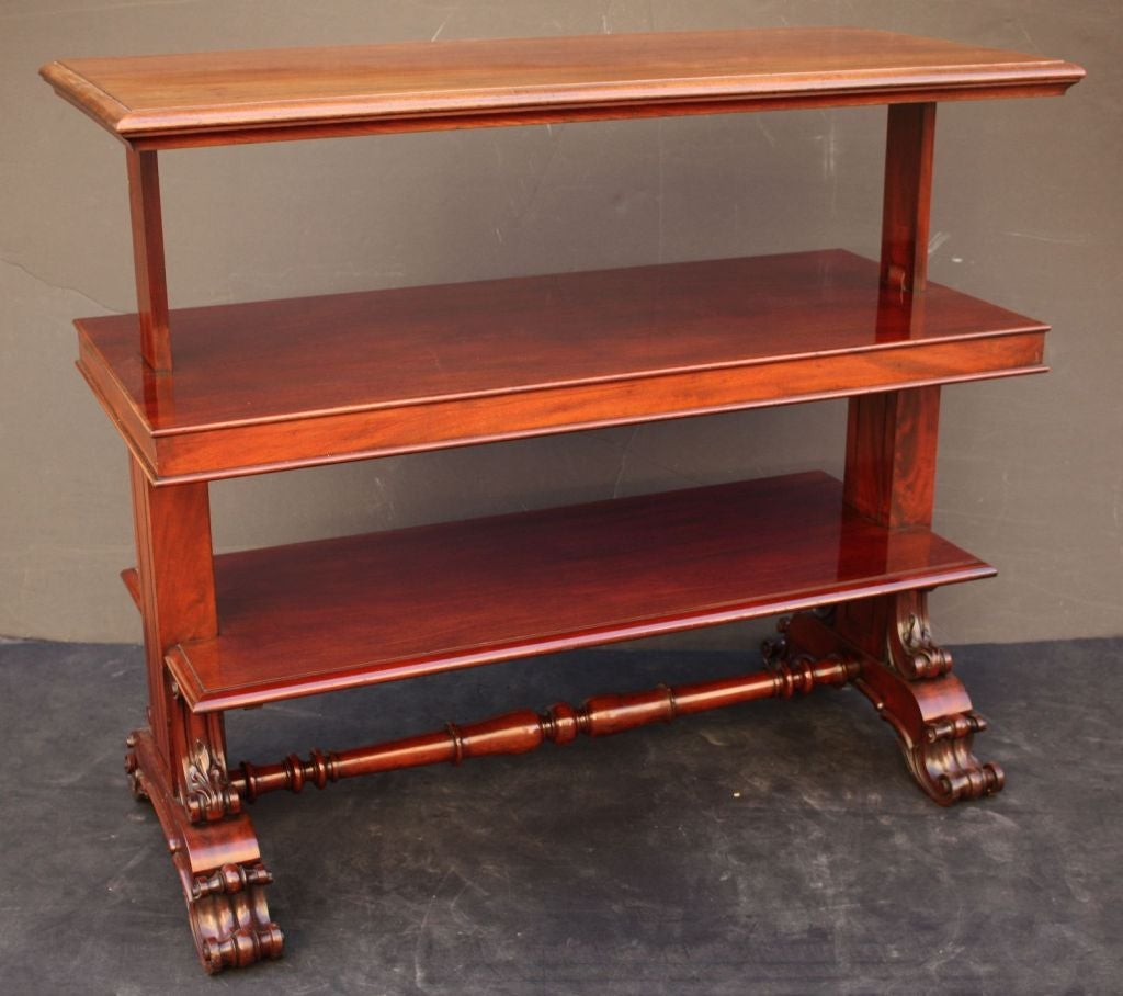 """A handsome English telescopic buffet table or console server of mahogany. The moulded rectangular top enclosing three tiers when in table form, telescoping upward to create three shelves when opened and """"locked"""" -  resting on carved scroll-work"""