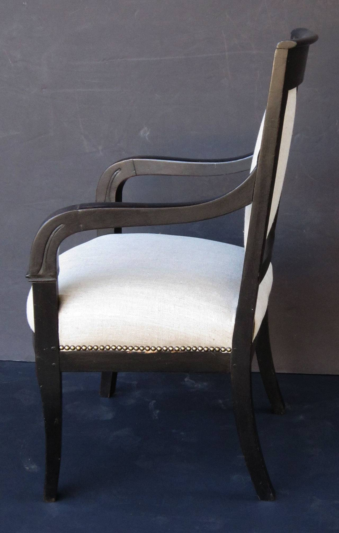 A handsome French ebonized mahogany desk chair (or armchair) featuring an upholstered back and seat with nailhead trim.  Elegant serpentine arms with carved designs in the Greek Revival style.