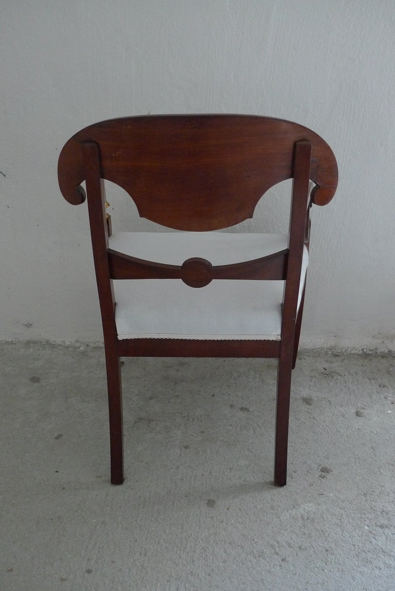 A set of 6 Empire dining chairs made in Sweden during the Karl Johan Period. Frame in mahogany with gilded flower detail on black splat. Newly upholstered.