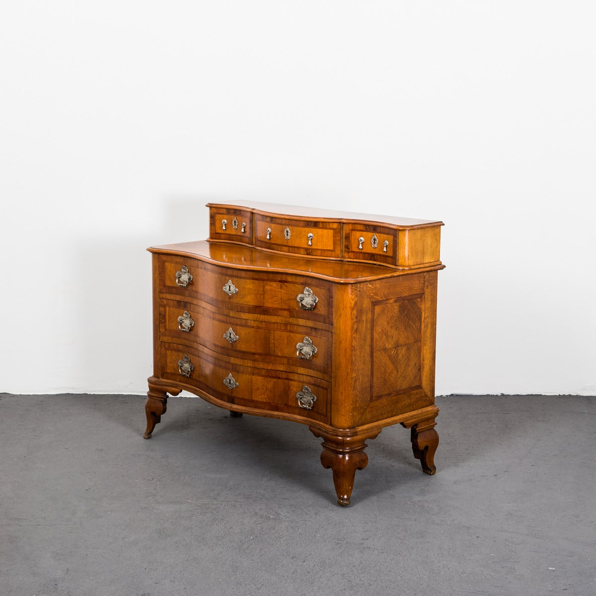A late baroque style chest of drawers with silver hardware. 3 larger drawers and 3 smaller drawers. Made during the 20th Century.