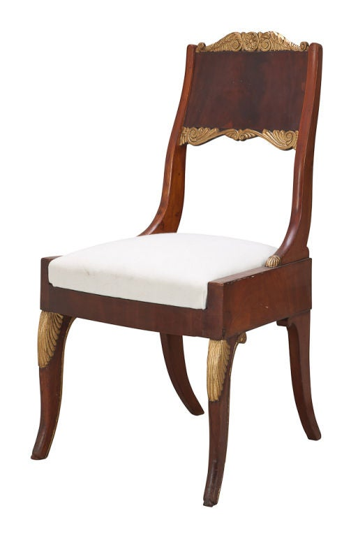 A pair of Russian side chairs made in mahogany with gilded details. Standing on back curved legs with leaf carvings.