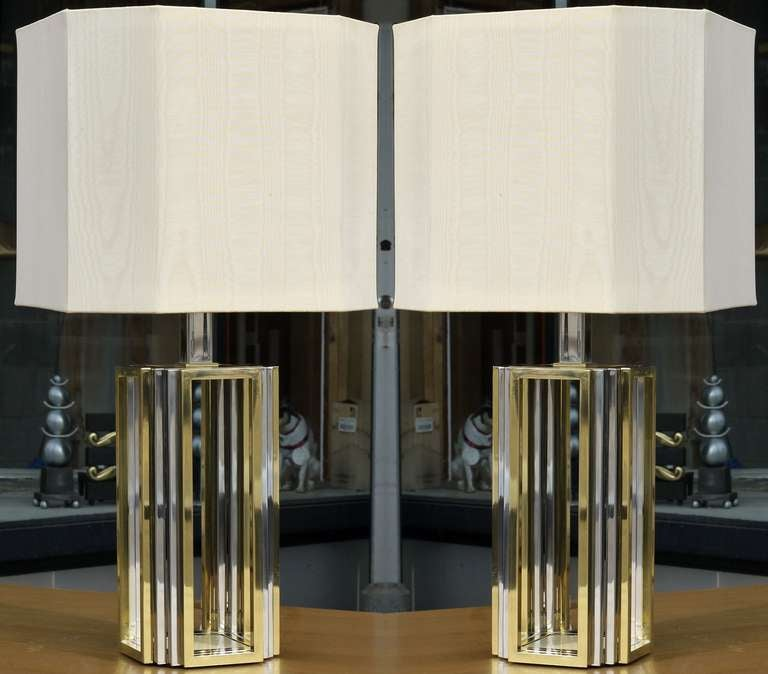 Stunning pair of Romeo Rega lamps in chromed steel and polished brass, featuring a 3 way switch to alternate between torchiere lighting and reading lights.  All the sockets have been replaced and updated.