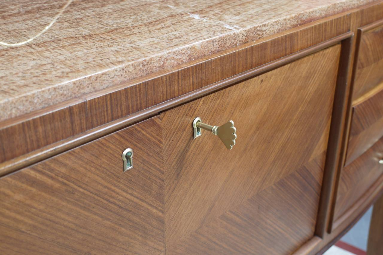 Stunning rosewood sideboard by Paolo Buffa with brass work attributed to Giovanni Gariboldi.  Stunning lines and proportions.  Every line on the piece works together harmoniously.   Brass gallery on the back measures 4 inches higher than piece and