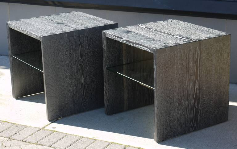 Pair of custom ebonized cerused oak end tables with dovetail solid wood construction and a built in glass shelf.  These were finished with silver mica in the grain which offers a subtle shimmer in the grain.  Could be used as end tables or night