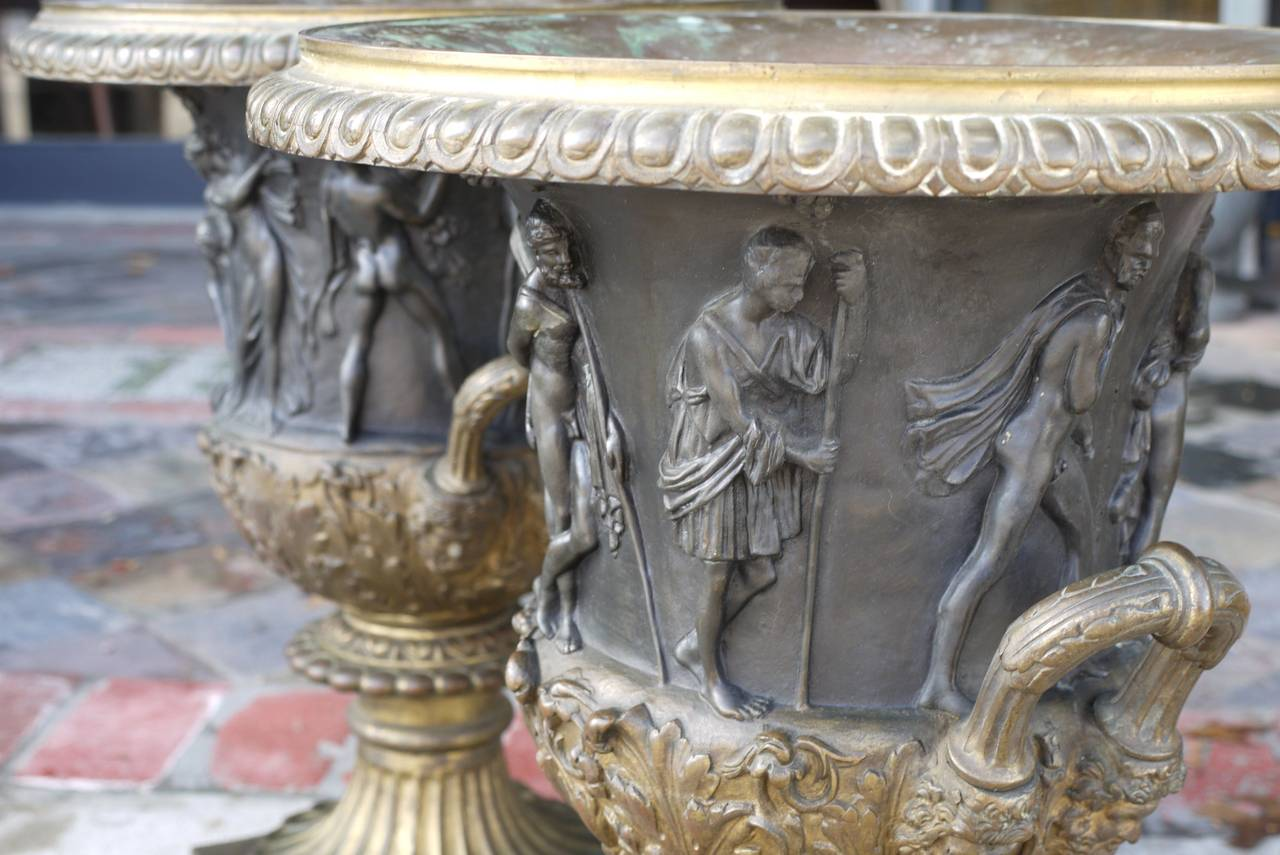 A pair of patinated and gilt bronze campana vases, after the Medici and Borghese models.  Classic egg and dart overhanging rim, above a waisted body cast in relief with a continuous scene of mythological figures, the acanthus lower section flanked