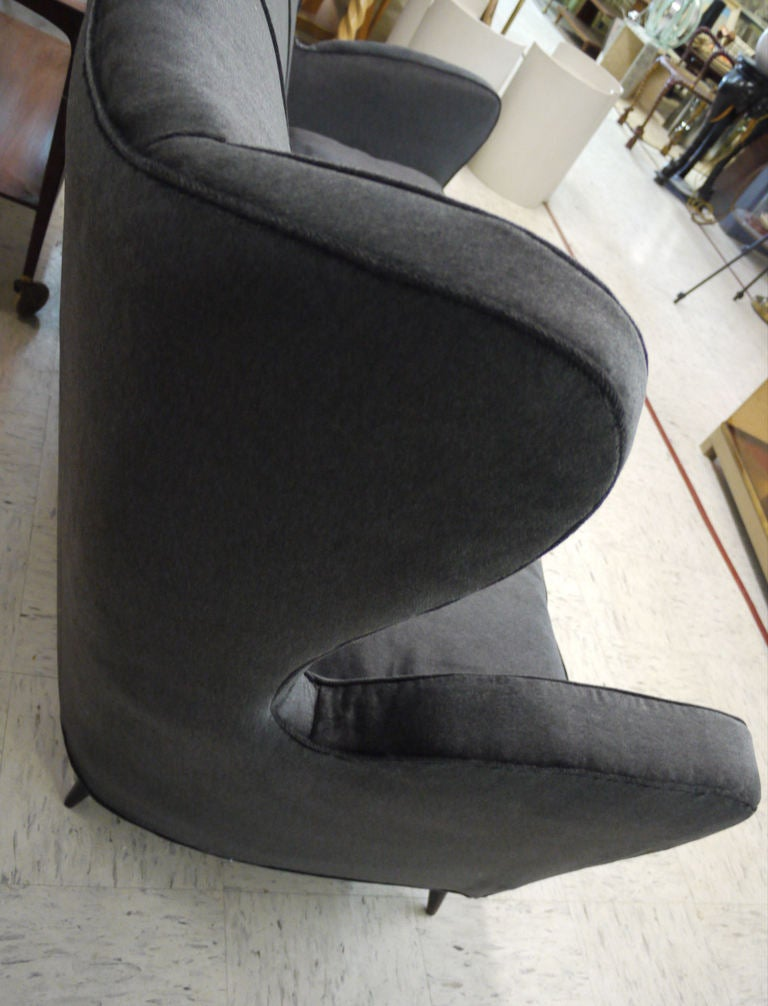 Elegant and graceful Italian sofa with winged back details and wooden cone feet.  Upholstered in a charcoal grey velvet with down cushions
