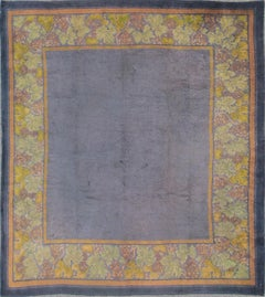 Antique Donegal Carpet from Ireland in solid Purple Background and Floral Border