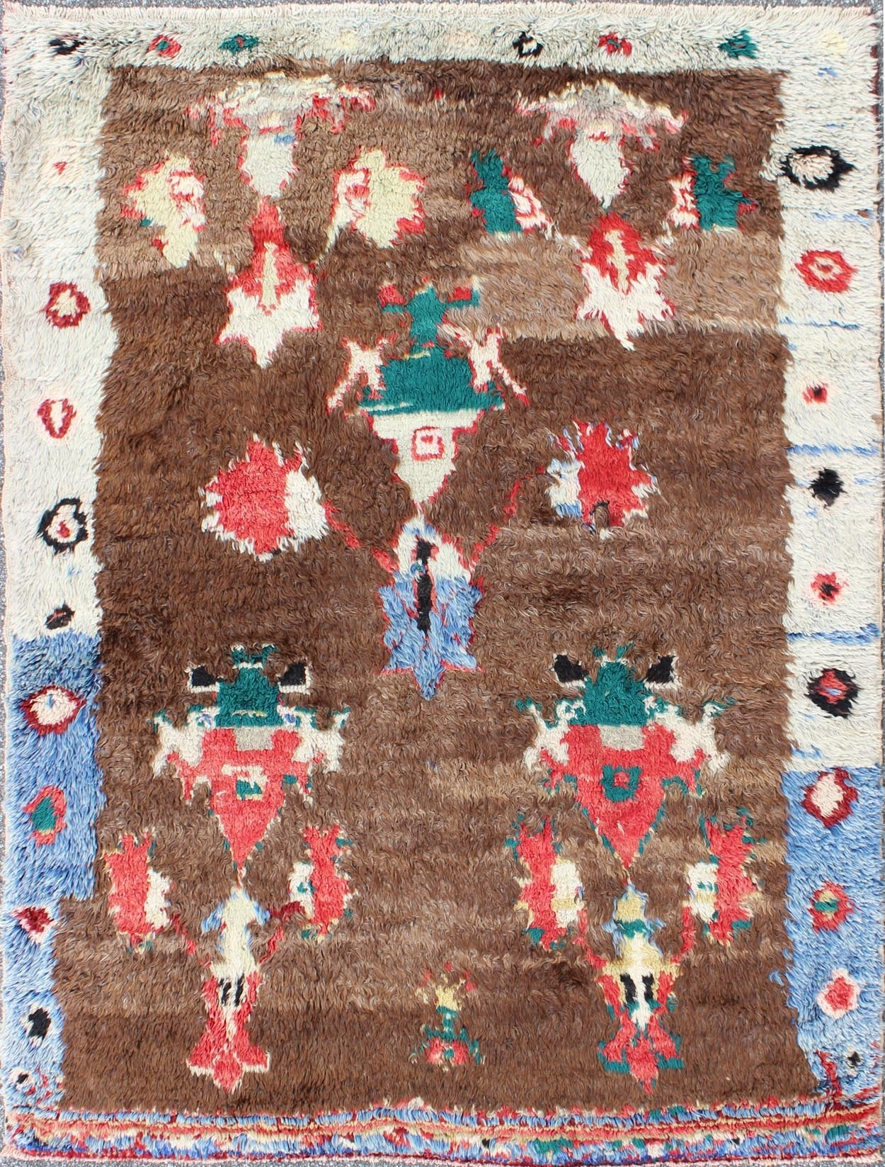 This antique Tulu rug showcases a free-spirited design with stunning colors of blue, brown, green, red and cream. The high pile of this rare rug is angora wool, which adds sheen to this eclectic piece.