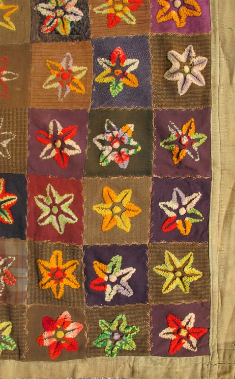 This spectacular late 19th century American quilt bears a colorful patchwork pattern of square-shaped fields, each displaying an array of star-shaped floral blossom motifs. A simple neutral border discreetly finishes this highly decorative piece of