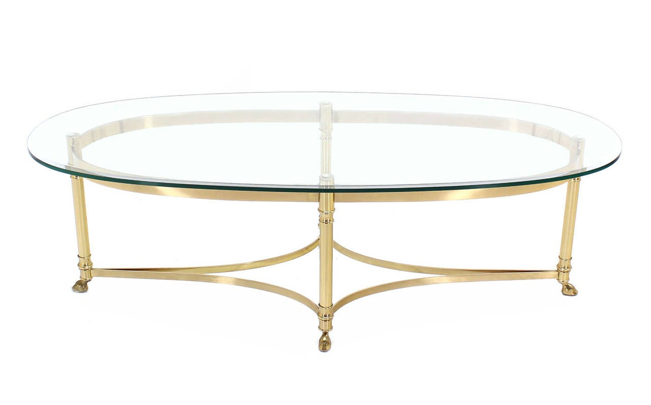 brass base and glass-top oval coffee table with hoof feet at 1stdibs