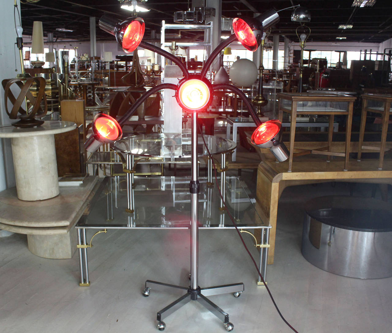Very unusual Mid-Century Modern chrome base four flexible arms lamp. Currently showed with five red heat bulbs.