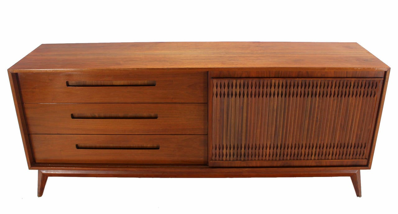Nice long walnut credenza with carved tambour pattern sliding door. Excellent vintage condition.