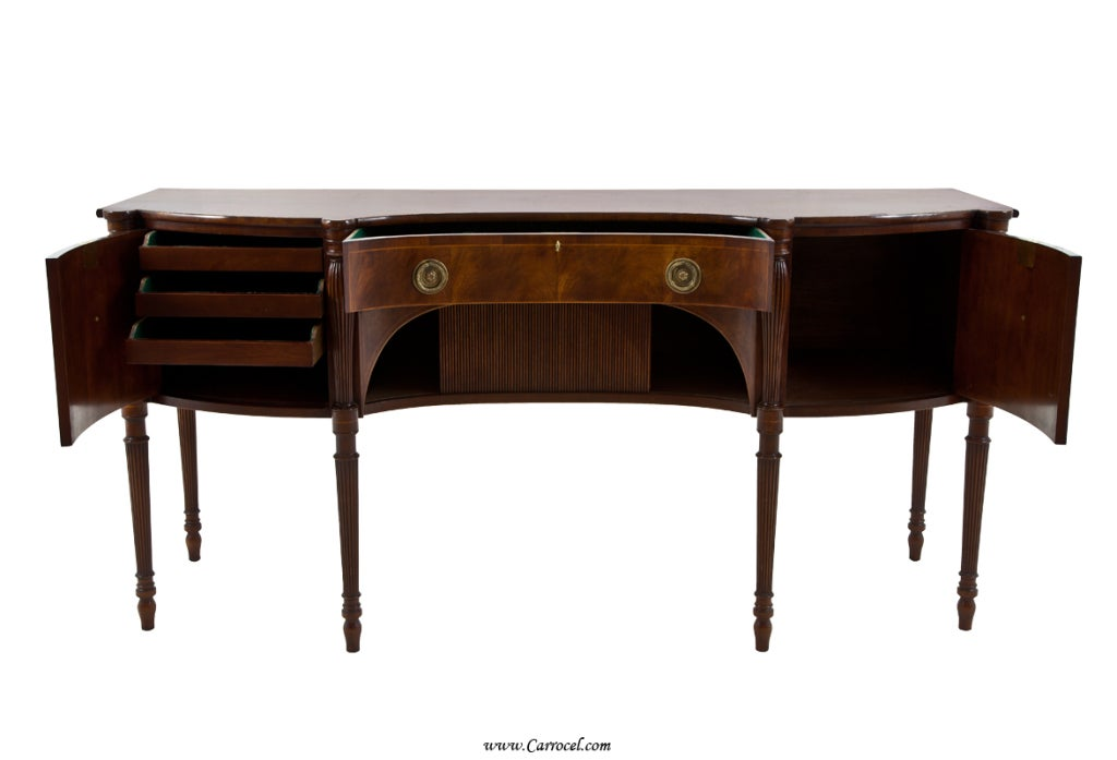 This beautiful mahogany sideboard features stunning mahogany veneers, carefully crafted fluted legs, solid brass hardware and a tambour sliding centre door.  Made in the early 20th century by Schmieg and Kotzian, this piece is exceptionally well