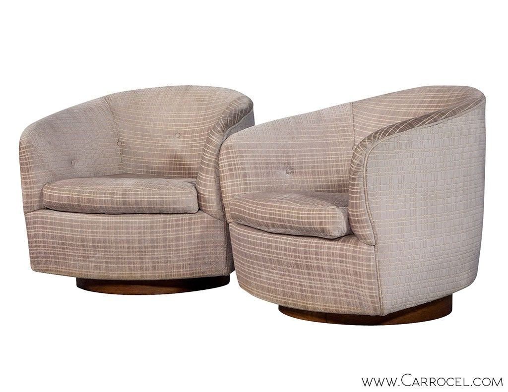 Two signature Milo Baughman swivel chairs designed for Thayer Coggin, bearing the seal of authentication. With tufted barrel backs flowing into stylish arms, walnut pedestals, original running upholstery over the seats, arms and backs, and Milo