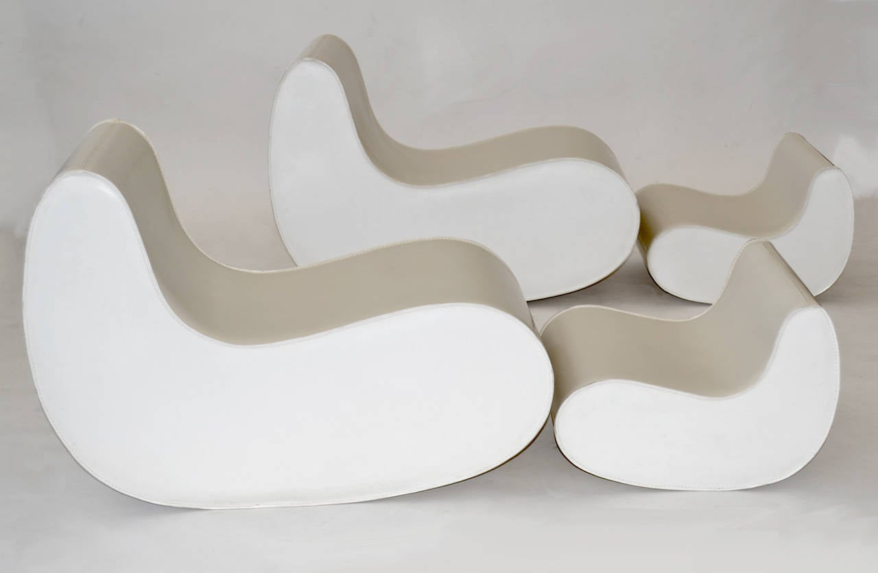 Four-piece, modular multi-use set by Kundalini which, when placed in various assemblages vertically or horizontally, form two soft rocking chairs, a sitting island, ottomans and/or side tables, or a mixture of all. Stitched white leather.