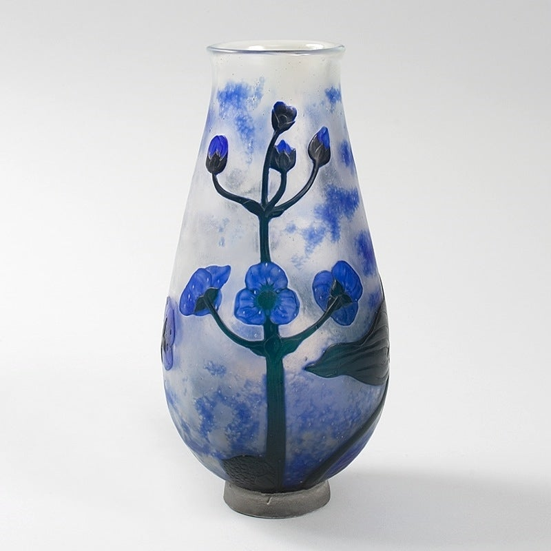 """A French Art Nouveau cameo glass vase by Daum featuring deep blue flowers on a mottled white and blue ground. The vase has both wheel-carving and martelé techniques.  circa 1910.  Signed, """"Daum Nancy"""" with the Croix de Lorraine.   (MG #10416)"""